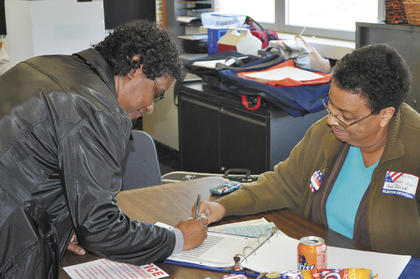 Precinct worker Ann Taylor shows Victoria Faye Williams where to sign in the voter registration book.