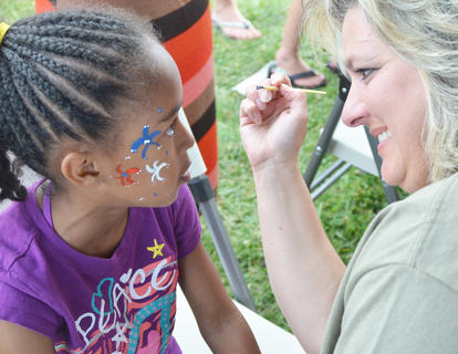 Lisa Young of Elk Horn Baptist Church paints fireworks on Amina Vazquez's face at the Family Fun Zone. Vazquez, 7, comes to Campbellsville from Georgia every year to visit family members and attend the community's annual Fourth of July celebration.