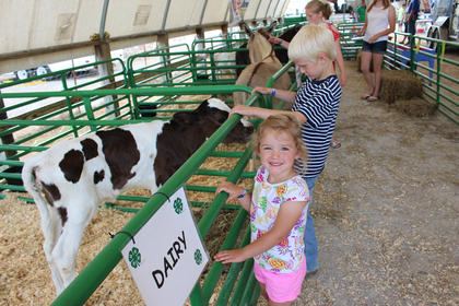 Sophie Myers and Bronson Cox smile while checking out the dairy calves at the Taylor County 4-H and Heavenly Haven Farm petting zoo.