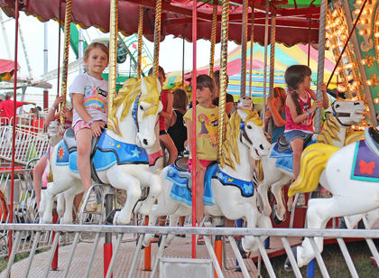From left, Ellie Wise, Madie Gebler and Lilly Wise ride horses on the carousel.