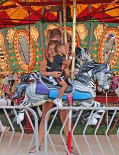 Sandra Price holds tight to her son Junior Price as he rides a horse on the carousel.