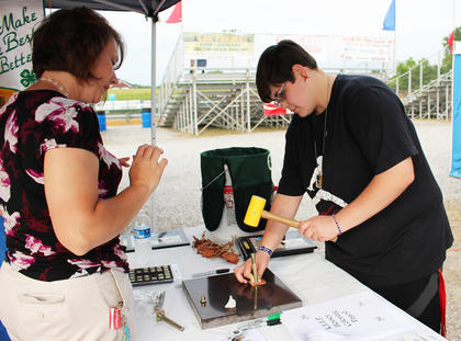 Breanna Shofner uses a hammer to stamp her initials into a leather keychain with the help of Marsha Woodrum at the Taylor County 4-H booth.