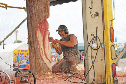 World champion chainsaw carver Dennis Beach creates a traditional wood spirit face out of wood.