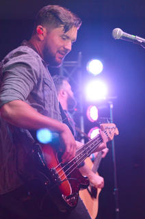 Dustin Daniels plays the bass guitar.