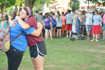 CU freshmen Kelli Evans, at left, and Abagael Murphy, both of Marion County, pray together as they hug during the prayer service. Evans is a band member and Murphy plays volleyball.