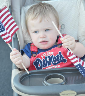 Brody Michael Etherington, 17 months, of Campbellsville, waves an American flag on Main Street before the annual Fourth of July parade on Friday.