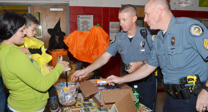 Campbellsville Police Officer Charlie Houk, at left, and Sgt. Shannon Wilson pass out candy at the annual Halloween Bash at Taylor County Elementary School. The event was hosted by Q-104 and local emergency services personnel.