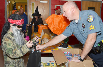 Campbellsville Police Sgt. Shannon Wilson passes out candy at the annual Halloween Bash at Taylor County Elementary School. The event was hosted by Q-104 and local emergency services personnel.
