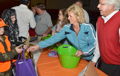Taylor County Judge/Executive Eddie Rogers and his wife, Theresia, pass out candy at the annual Halloween Bash at Taylor County Elementary School. The event was hosted by Q-104 and local emergency services personnel.
