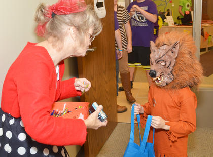 Taylor County Public Library Outreach Librarian Bonnie Webster passes out candy on Thursday to scary creatures.
