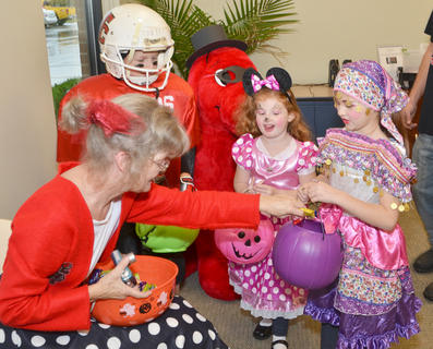 Taylor County Public Library Outreach Librarian Bonnie Webster passes out candy on Thursday to football players, gypsies and even a mouse.