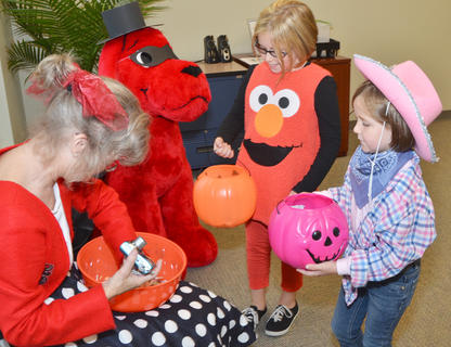 Taylor County Public Library Outreach Librarian Bonnie Webster passes out candy on Thursday to local children.
