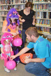 Kyle Brewer passes out candy to little monsters at the library.