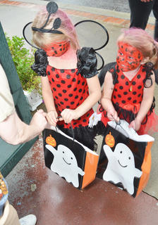 Grace Waymon, 5, at left, and Cecilia Waymon, 3, dressed as ladybugs, ask for some candy while trick-or-treating on Main Street.