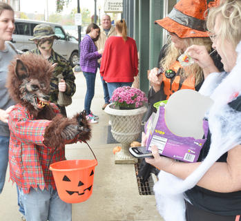 Candy Bouquet employees give some candy to Ansley Bell, 7, of Campbellsville, who dressed as a wolf.