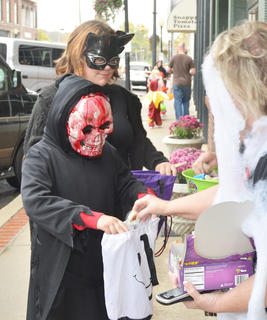 Candy Bouquet employees pass out candy to scary creatures on Main Street.