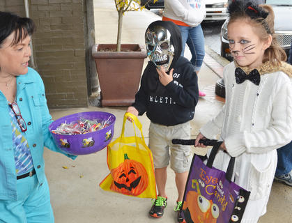 Emerson Dengel, 5, at left, and Isabel Dengel, 7, of Campbellsville, ask for some treats at Mitchell's Men's Wear on Main Street.