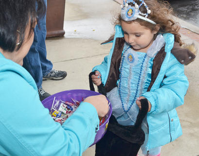 Erika Underwood, 2, of Campbellsville, dressed as Cinderella, gets some candy at Mitchell's Men's Wear on Main Street.