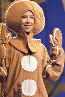 Baylie Skaggs dresses as a gingerbread man during a song.