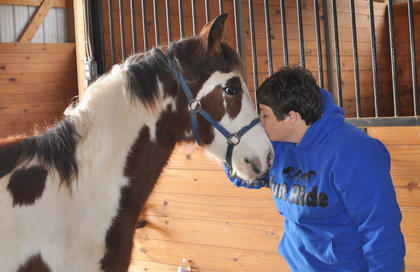 Owner Leisha Holzknecht gives Missy, a Tennessee Walking Horse, a kiss at Stoner Creek Farm.