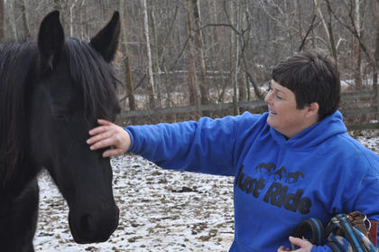 Owner Leisha Holzknecht gives Sun, a Tennessee Walking Horse, a friendly rub.