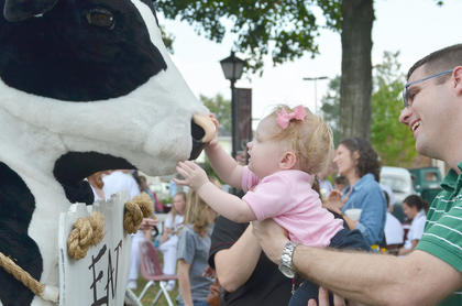 Anna Kruer, 9 months, daughter of CU alumni Holly Kruer, who graduated in 2004, and Doug Kruer of New Albany, Ind., at right, gives the CU Chick-fil-A cow a kiss on the nose during Saturday's homecoming festival on Stapp Lawn.