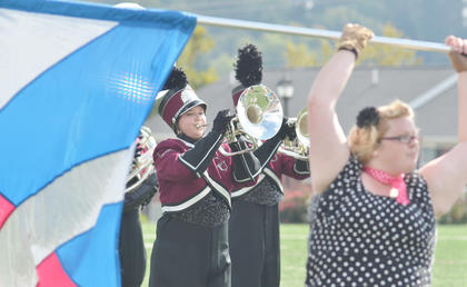 CU Tiger Marching Band member Holli Lindsey of Scottsville plays during Saturday's halftime show. At right is color guard member Megan Hill of Springfield.