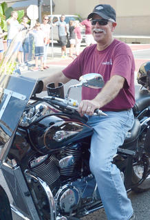 Ed Pavy, CU's director of campus ministries, drives his motorcycle during Saturday's homecoming parade.