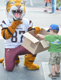 CU's mascot, Clawz, greets children during the parade. Here, Brian Coury, 2, gets some candy from Clawz. Coury is the son of Philip and Katy Coury. Mr. Coury attended CU from 2008 to 2010.