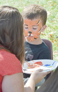 CU sophomore Brooklyn Roby of Campbellsville, a member of the Art Club, paints tiger faces during Saturday's homecoming festivities. Above, Elijah Rodgers, 6, of Campbellsville, gets his face painted.