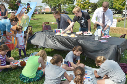 CU students paint pumpkins with local children at CU's homecoming festival on Stapp Lawn.