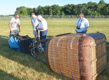 From left, Allen Gaddis and Tom McClendon help hot air balloonist John Herbst inflate the balloon in which Herbst and and CKNJ Staff Writer Calen McKinney, at right, rode.