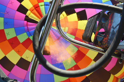 A view from inside a hot air balloon as it climbs higher into the air.