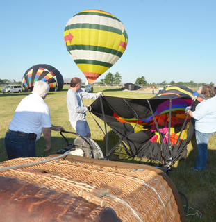 From left, Tom McClendon and CKNJ Staff Writer Calen McKinney help hot air balloonist John Herbst inflate the balloon in which Herbst and McKinney rode.