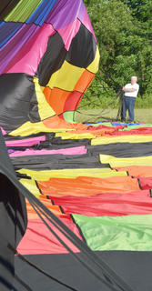 Hot air balloonist John Herbst works to gather his hot air balloon after he and CKNJ Staff Writer Calen McKinney landed.