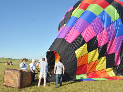 From left, CKNJ Staff Writer Calen McKinney, hot air balloonist John Herbst, Tom McClendon and Allen Gaddis prepare to deflate the hot air balloon in which Herbst and McKinney rode after their landing.