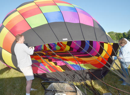 From left, Tom McClendon and CKNJ Staff Writer Calen McKinney help inflate the balloon in which John Herbst and McKinney rode.