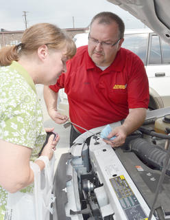 Carl Hicks of Advance Auto Parts in Campbellsville shows Cheryl Crenshaw of Liberty how to check the oil in her vehicle.