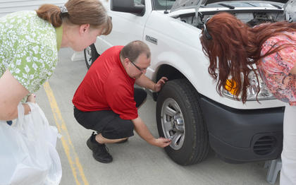 Carl Hicks of Advance Auto Parts in Campbellsville shows Cheryl Crenshaw, at left, and Lara Howard of Liberty how to check the pressure in a tire.