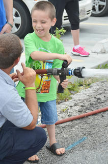 Hunter Wilson of Columbia laughs as he learns how difficult it can be for a firefighter to spray a water hose.