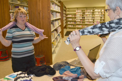 Tammy Blakeman learns one of the many ways to tie a scarf from Cindy Harvey.