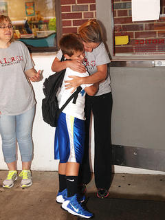 Jonathan Vaughn, a 9-year-old fourth-grader at Taylor County Elementary School, gets a hug from Jennifer Gabehart, his former kindergarten teacher, on the first day of school Wednesday.
