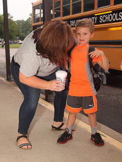Kindergartener Steven Morgan is greeted by preschool teacher Brandy McCubbin as he arrives at school on Wednesday.