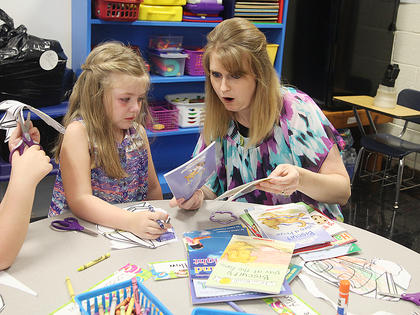 Taylor County Elementary kindergarten teacher Chanci Patterson talks with Frehley Whitlow about some of the books available in her class.