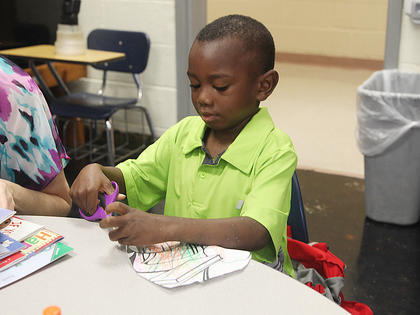 Campbellsville Elementary School kindergartener Trae Alexander cuts paper on the first day of school.