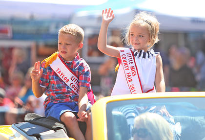 Cross Watson and Ella Owens, Little Mister and Little Miss Taylor County Fair 2014, wave as they ride in the Fourth of July parade Friday.