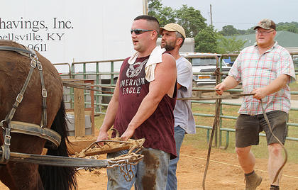 Todd Ellis, Joey Ellis and Mark Stoltman work a team of mules at the fair Saturday.