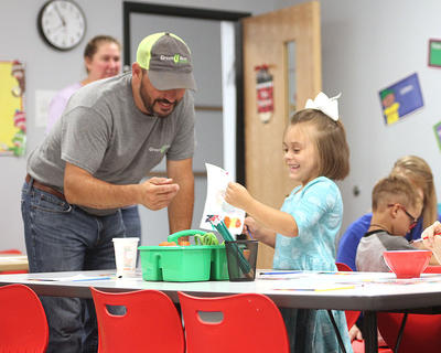 Hadlee Lee, 5, shows her dad, Steven Lee, a picture she painted as school began Wednesday morning at Taylor County Primary Center.