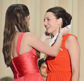 Brittany Salmon, who won the DYW competition last year, places a medal around Katelyn McMahan's neck after McMahan is named Taylor County's Distinguished Young Woman for 2014.