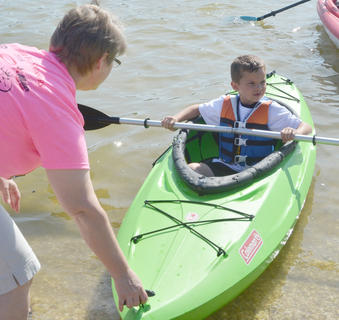 Susan Wise of Campbellsville helps Harlee Thompson, 5, of Greensburg, learn to paddle a kayak.